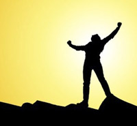 Picture of a man in shadow standing on a rocky hill with his arms raised victoriously in a V