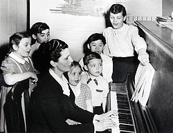 kids standing around a woman playing the piano