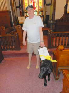"Lenny with Guide Dog Toga with sign on her harness that reads ""walk a mile in her shoes"". as he presents program to his church."