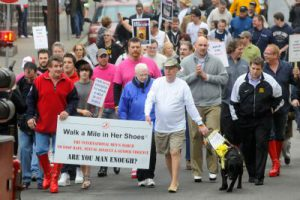 "Lenny McHugh & friend George Moyer ( both top fundraisers) carrying the ""Walk a mile in her shoes"" banner. Alongside Lenny, Guide Dog Toga with sign on her harness that reads ""walk a mile in her shoes""."